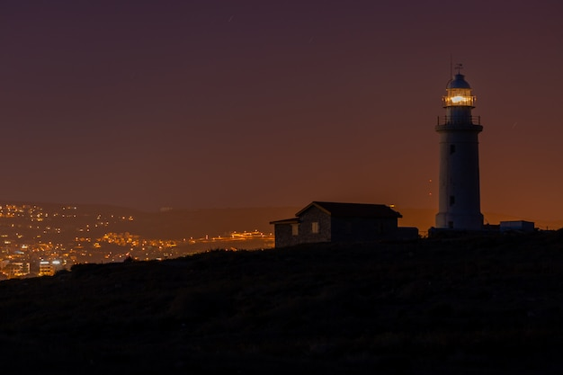 Beautiful view of a lighthouse and a house on a hill captured at night in cyprus