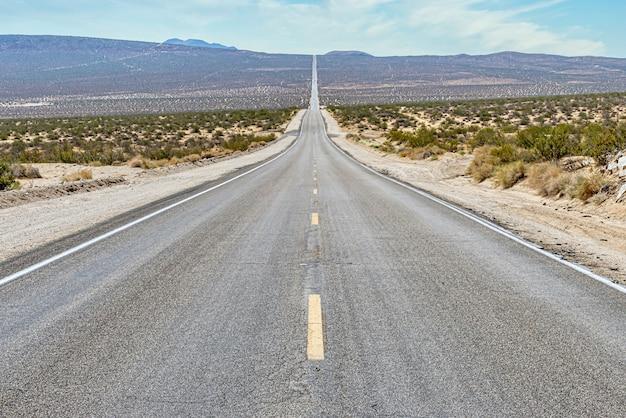 Bella vista di una lunga strada di cemento rettilinea tra il campo del deserto