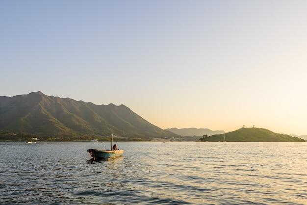 Bella vista di un motoscafo sulla superficie calma del mare vicino alle montagne