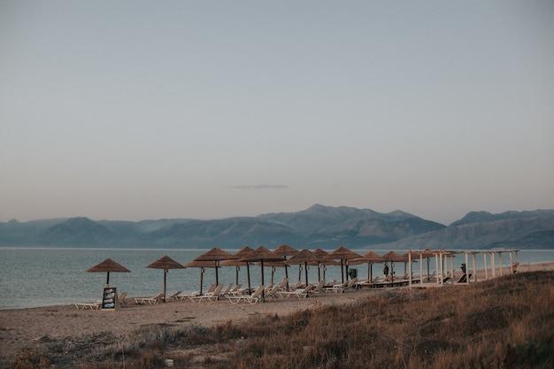 わらのビーチパラソルの下にデッキチェアがあるビーチの美しい景色