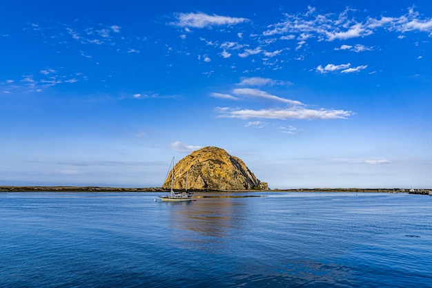 Прекрасный вид на лодку возле острова посреди океана под голубым небом