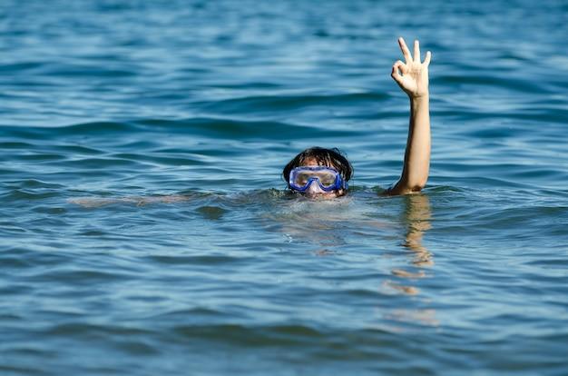 頭と片方の腕だけを水から出して湖を泳ぐ女性の美しい景色