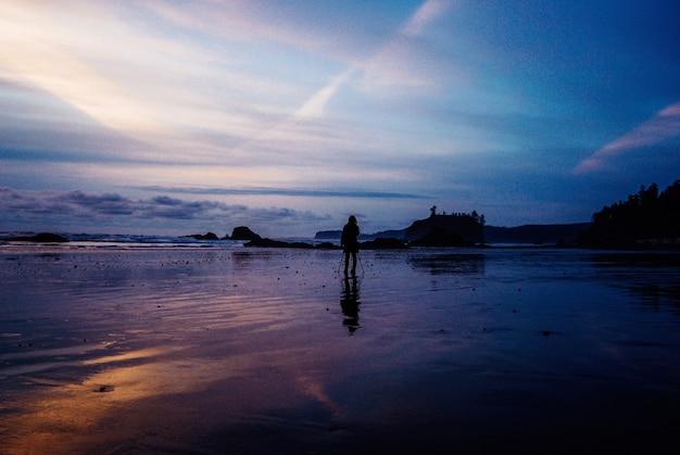 夕暮れの海の近くの濡れた砂の上に立っている人の美しい景色
