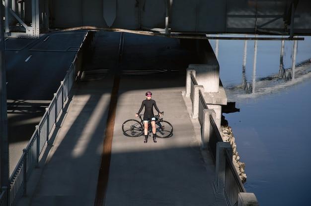 Прекрасный вид позирующей спортсменки с велосипедом