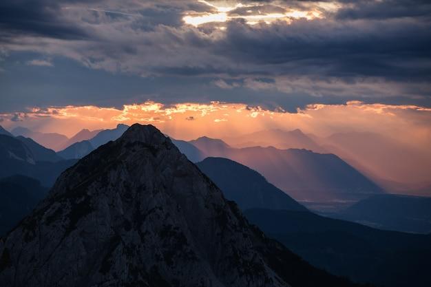 일몰 동안 흐린 하늘 아래 산의 실루엣의 아름 다운보기
