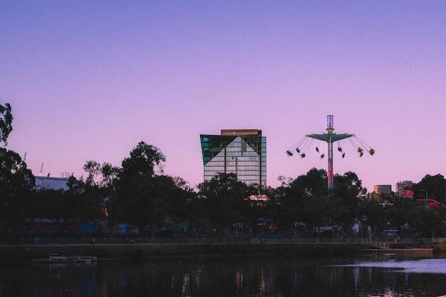 側に背の高いスイングのある背の高いガラスのビジネスビルの美しい景色