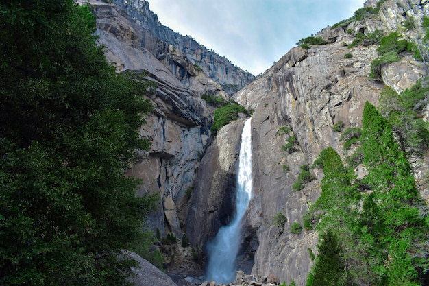 Прекрасный вид на водопад, вытекающий из скалы и вливающийся в великолепные зеленые пейзажи