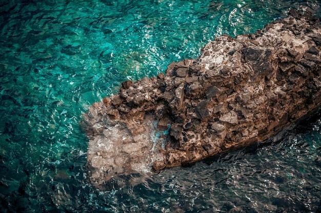 Прекрасный вид на большую скалу в волнистом бирюзовом море