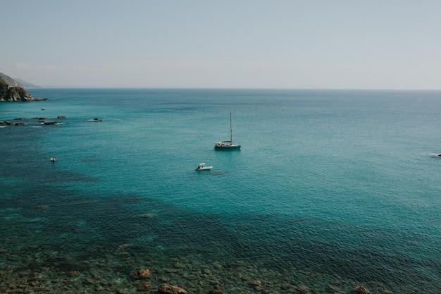Прекрасный вид на лодки в бирюзовой воде с ясным горизонтом