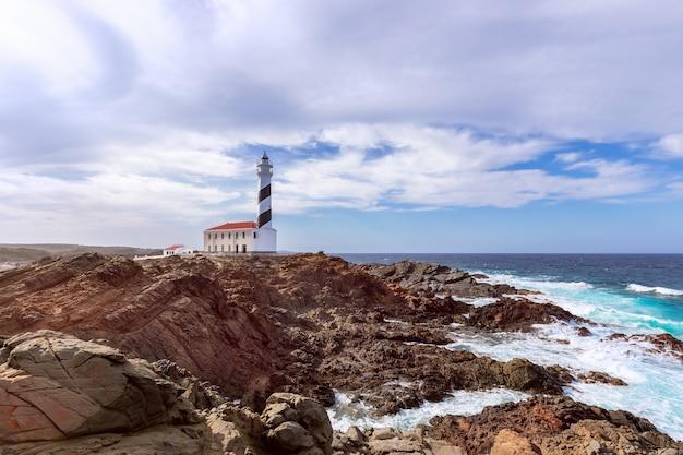 Прекрасный вид на знаменитый маяк фаро-де-фавариткс под небом с облаками на острове менорка, балеарские острова, испания