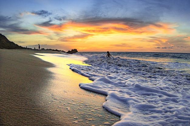砂浜を洗う泡の波の美しい景色
