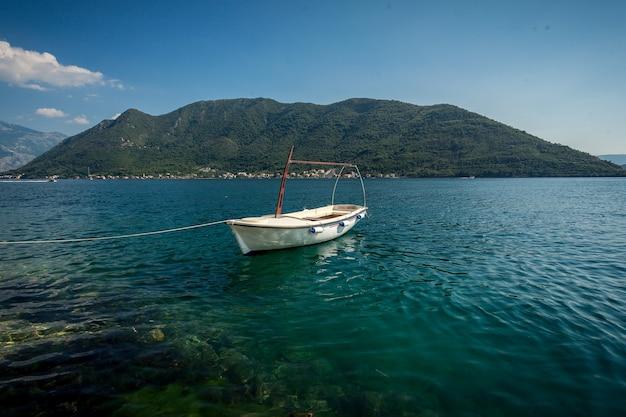 Прекрасный вид на которский залив с пришвартованной белой деревянной гребной лодки