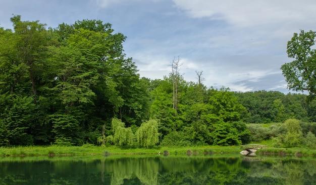 緑豊かな自然の美しい景色とザグレブ、クロアチアのマクシミール公園の水に反映