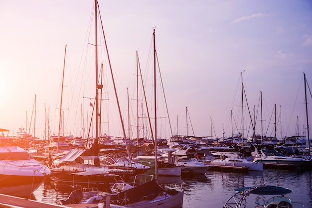 マリーナとヨットやモーターボートの港の美しい景色。海に沈む夕日。