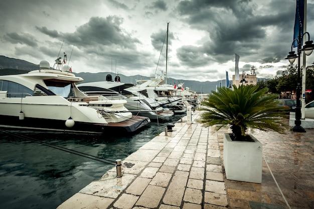 Прекрасный вид на пришвартованные роскошные яхты в пасмурный и дождливый день