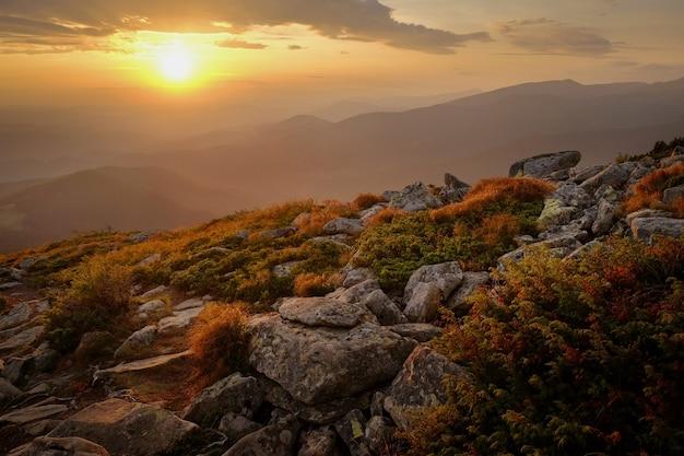 秋のカルパティア山脈の前景に岩と夕日の山の風景の美しい景色