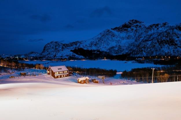 ロッキー山脈に囲まれた雪に覆われた小さな赤い家のあるノルウェーの村の美しい景色。ロフォーテン諸島の冬の夕暮れ。
