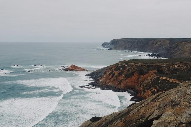 Прекрасный вид на скалистую береговую линию с океаном под чистым небом