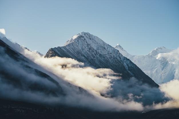 日差しの中で厚い雲の上に雪をかぶった山々の美しい景色。青い空の密集した低い雲の中に白い雪のピークがある風光明媚な明るい山の風景。雪に覆われた最高峰の素晴らしい景色。