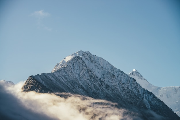 日差しの中で厚い雲の上に雪をかぶった山々の美しい景色。青い空の密集した低い雲の中に白い雪のピークがある風光明媚な明るい山の風景。雪の頂点のある素晴らしい景色。