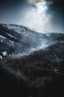 雪に覆われた高い山々に雲の切れ間から輝く太陽の美しい景色