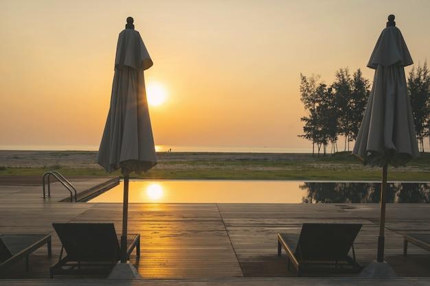 2つのサンベッド付きのスイミングプールエリアで夕日の美しい景色