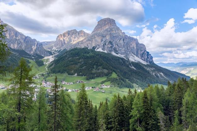 Прекрасный вид на альпийскую деревню кольфоско у подножия горы сассонхер.
