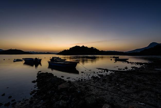 하늘의 석양 아래 해안가 보트의 아름다운 전망