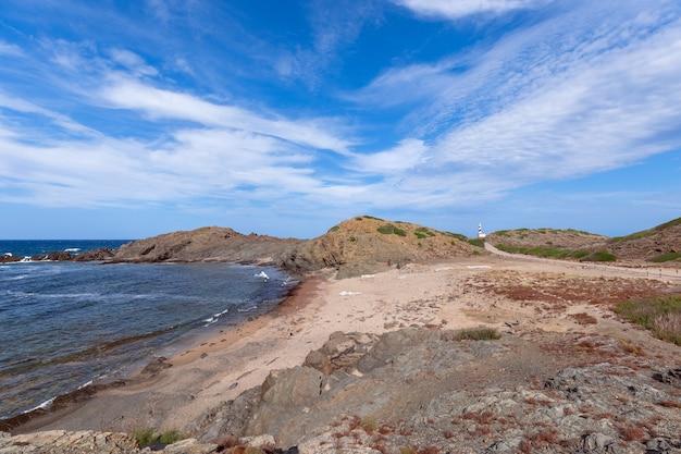 Прекрасный вид на спокойную бухту и маяк вдалеке на острове менорка, балеарские острова, испания.