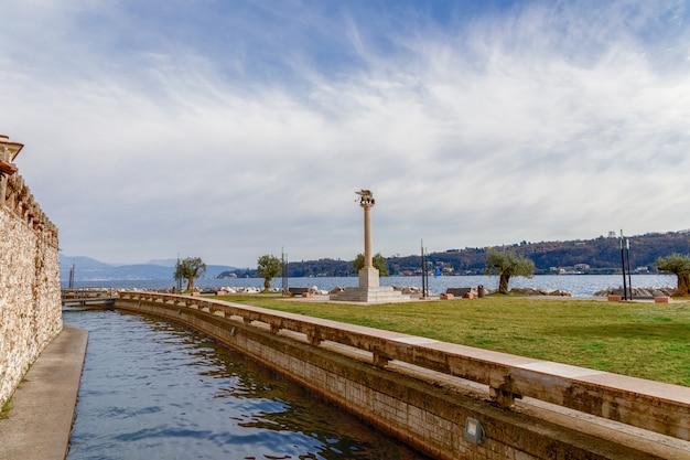 Прекрасный вид на канал и озеро гарда в городе сало. в центре композиции - символ города крылатый лев. ломбардия, италия