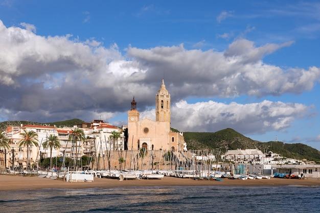 해변에서 보트와 시체스에있는 교회 sant bartomeu 및 santa tecla의 아름다운 전망