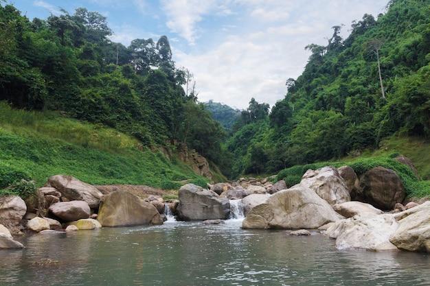 Прекрасный вид на зеленые горы и небольшой каскад водопадов в озеро.
