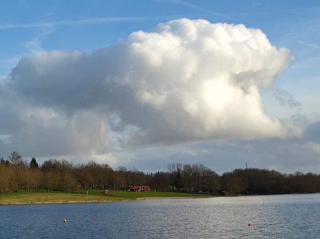 Прекрасный вид на озеро с пасмурным голубым небом на заднем плане