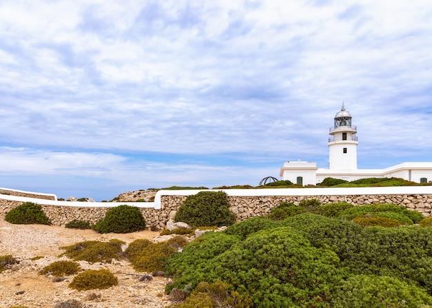 Прекрасный вид на маяк и облачное небо над ним. менорка, балеарские острова, испания