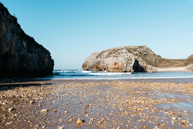 青い空の下でビーチ近くの岩に打ち寄せる海の波の美しい景色