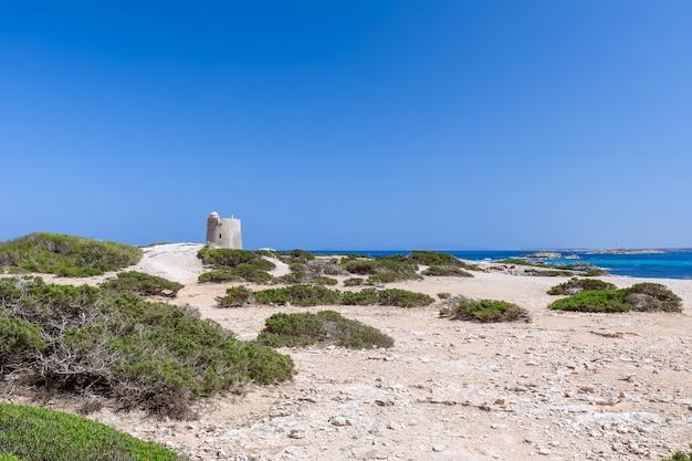 Прекрасный вид на старую смотровую башню torre de ses portes и маяк на побережье острова ибица. испания