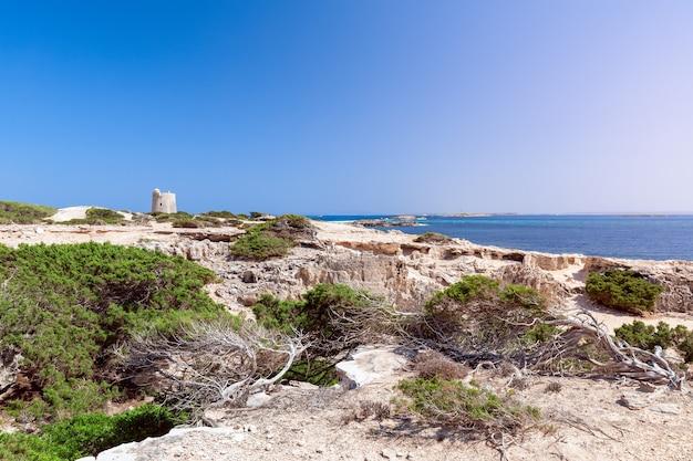 Прекрасный вид на старую смотровую башню torre de ses portes и скалистое побережье острова ибица. испания