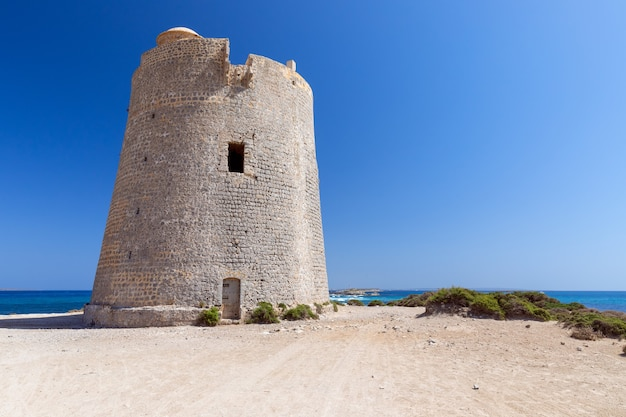 Прекрасный вид на старую смотровую башню torre de ses portes на побережье острова ибица. испания