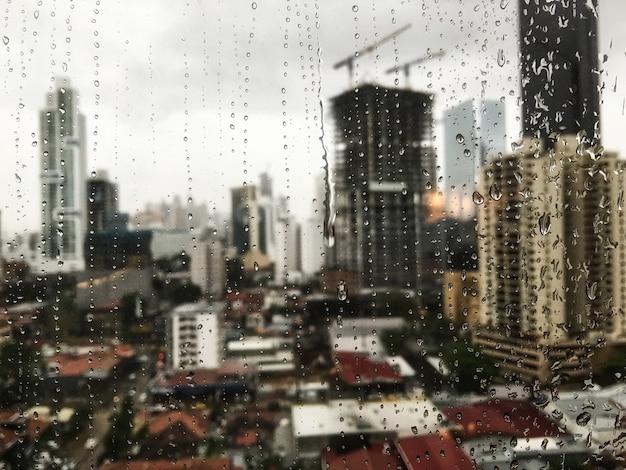 窓を転がる雨滴と表面の高層ビルの美しい景色