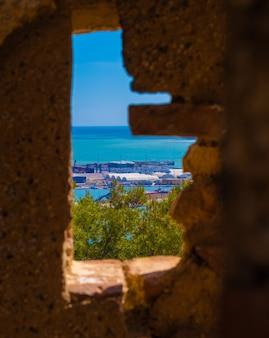 Прекрасный вид на море через историческое окно в замке гибральфаро в малаге