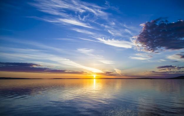 Красивый вид на море с солнцем, сияющим в синем небе на заднем плане