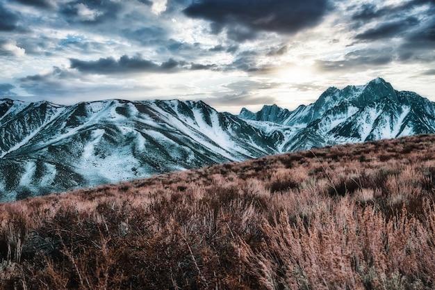 息を呑むような曇り空の下、雪に覆われた山々の美しい景色