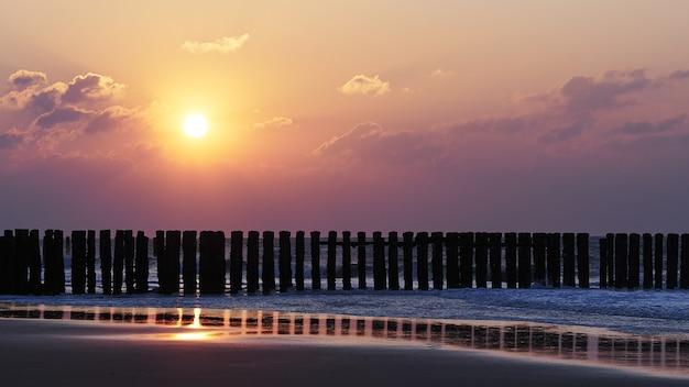 Прекрасный вид на закат с фиолетовыми облаками над пляжем
