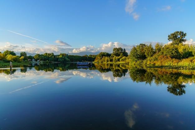 Прекрасный вид на деревья и небо, отражающееся в воде в солнечный день
