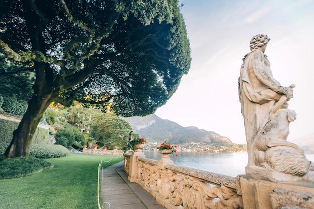 Красивый вид на виллу увиденную от озера como на заходе солнца, ломбардии, италии. взгляд красивой итальянской виллы на озере como в солнечном свете.