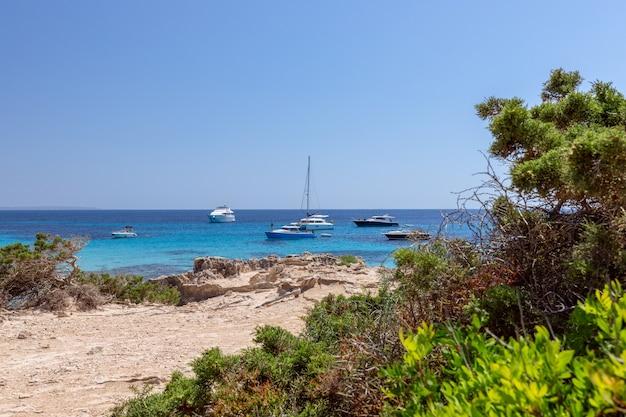 Прекрасный вид на бирюзовое море и яхты на побережье ибицы, испания.