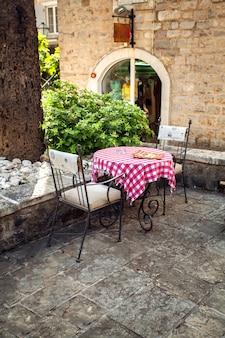 오래된 레스토랑의 여름 테라스에 두 개의 의자와 테이블의 아름다운 전망
