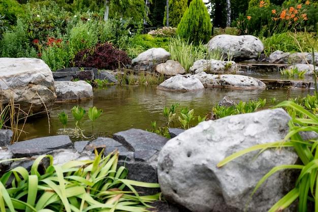 공식적인 정원에서 바위를 흐르는 물의 아름다운 전망