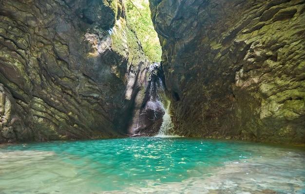 Прекрасный вид на пейзаж водопада. небольшой водопад в темно-зеленом лесу.