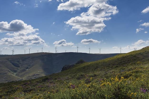 Прекрасный вид на ветряные мельницы на холме с пасмурным голубым небом